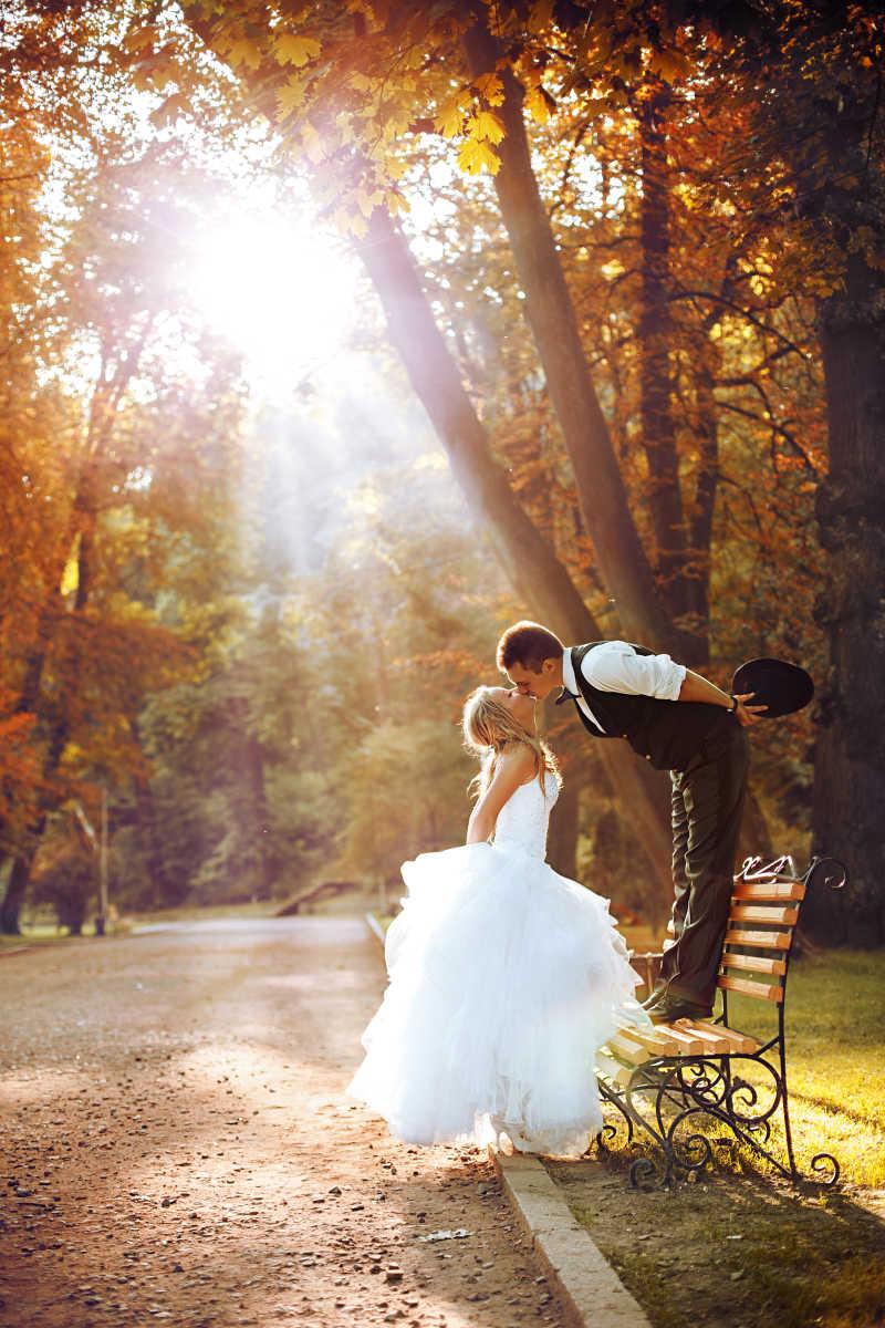 在公园接吻的新娘和新郎
