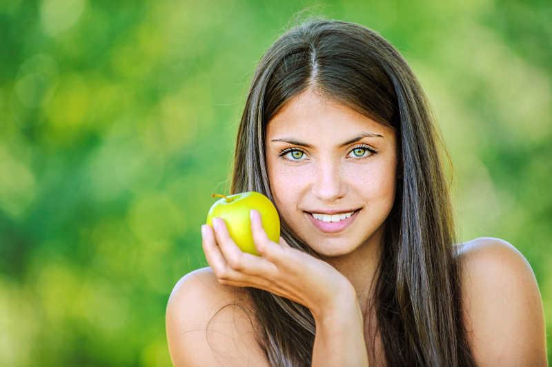 绿色背景下微笑的黑发美女手里拿着苹果
