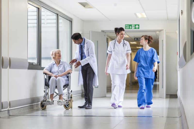 医院走廊医护人员与轮椅上的女患者