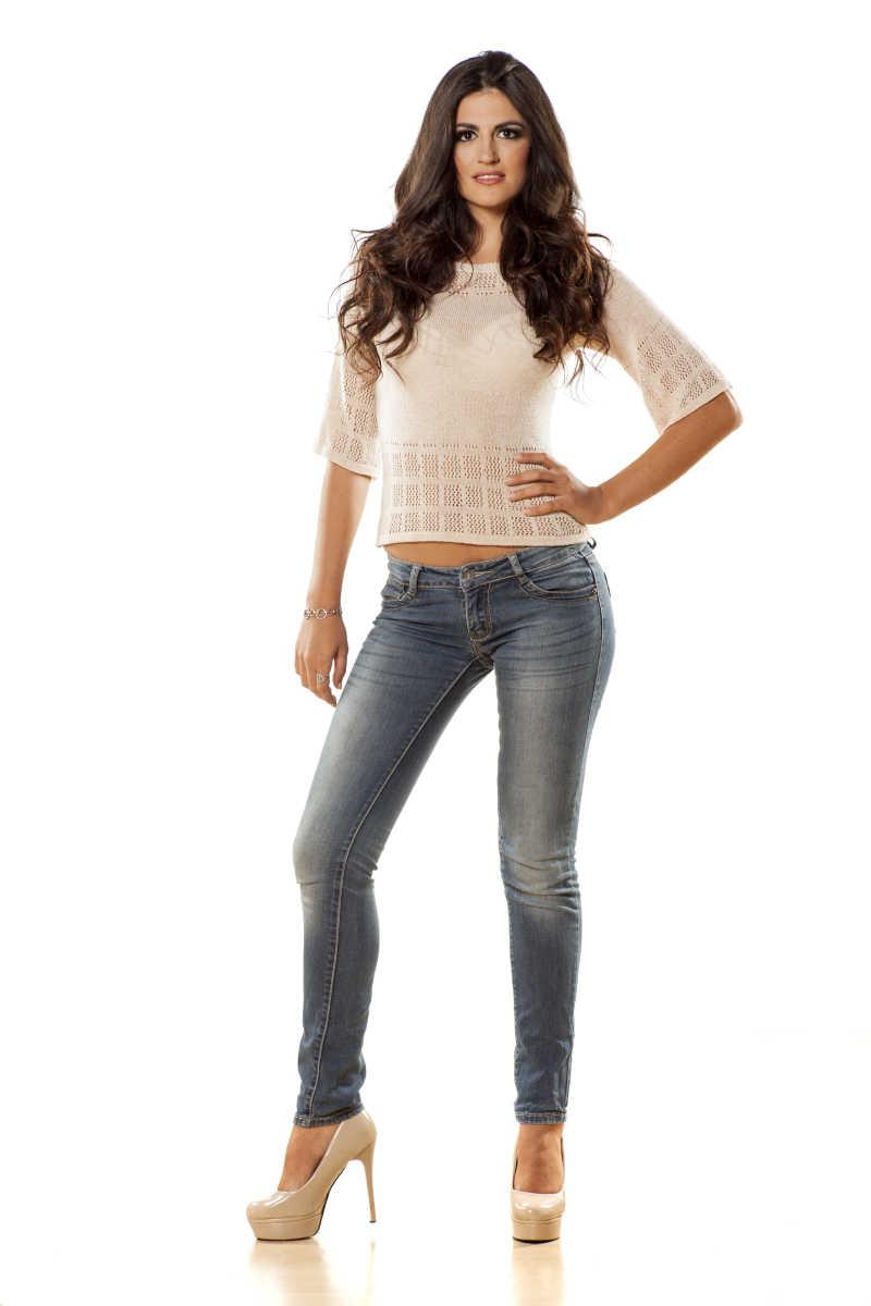 白色背景下穿着修身白T和牛仔裤的美女