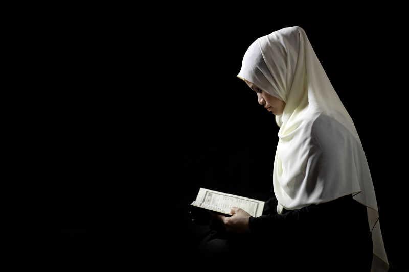 黑色背景上戴着白色头巾看着书本的穆斯林女性