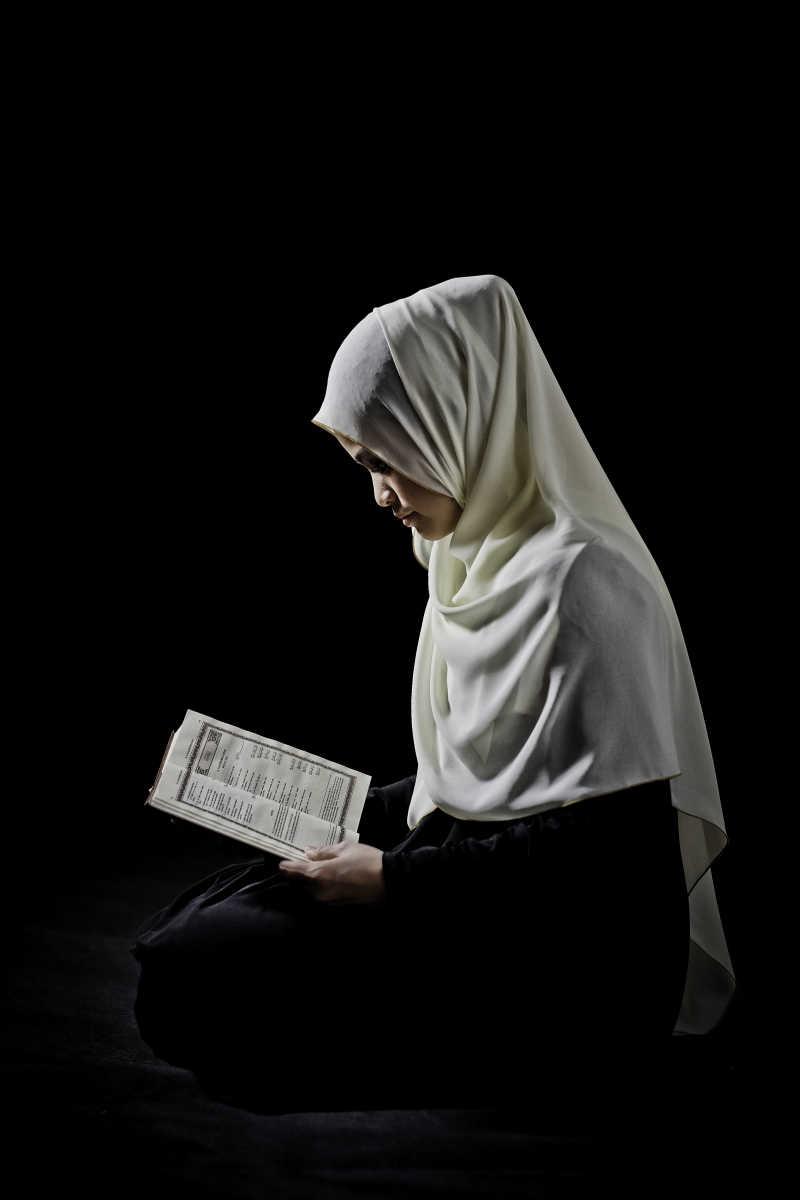 黑色背景上月兔古兰经的穆斯林妇女