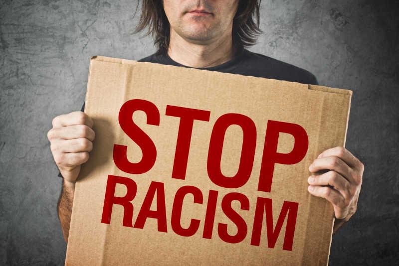 男子持纸板横幅与停止种族主义的信息