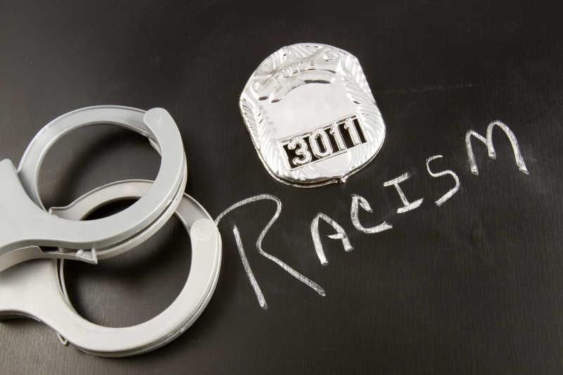 一个警察徽章和手铐旁边黑板上的种族主义