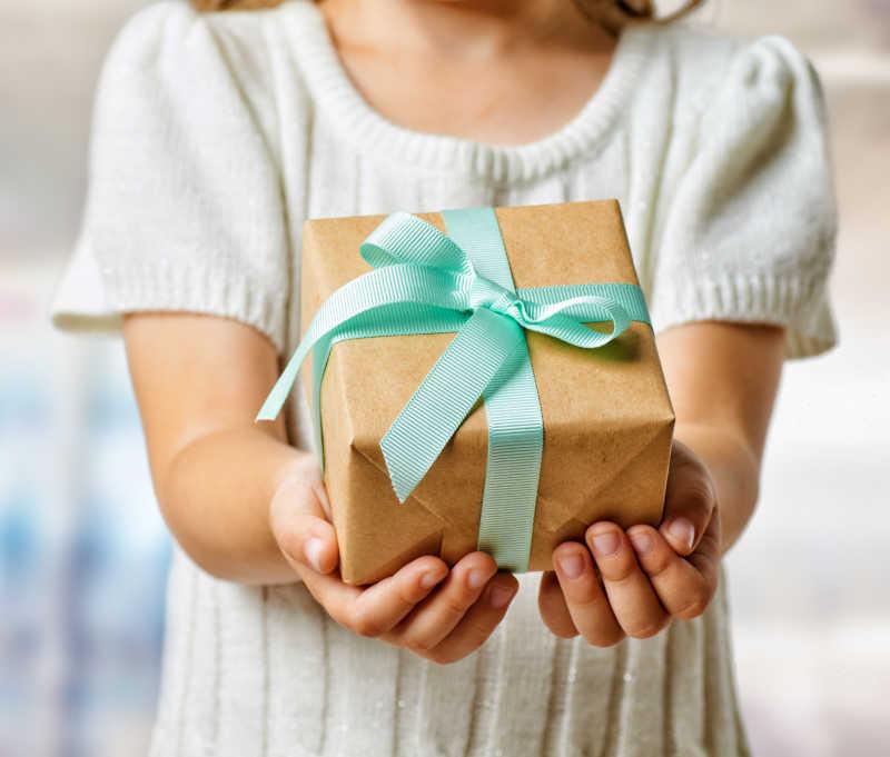 女人用双手捧着包装好的礼品盒