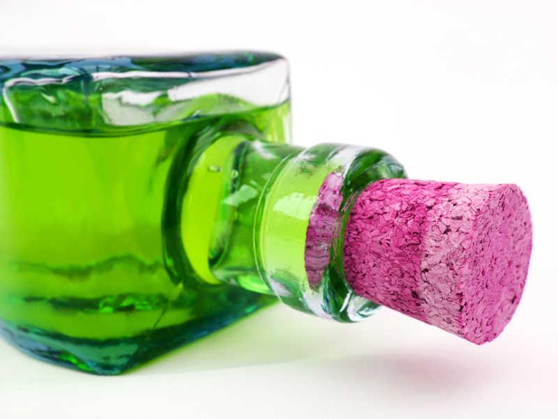 白色背景上塞着玫红色瓶塞的绿色玻璃瓶