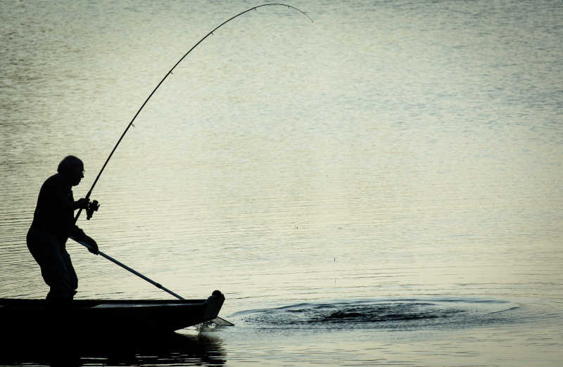 站在船上钓鱼的人