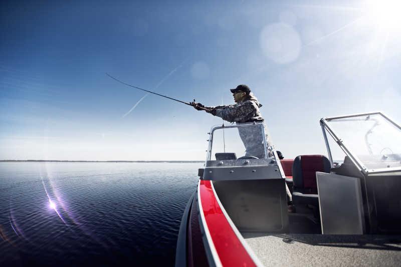 在船上拿着钓鱼竿钓鱼的男人