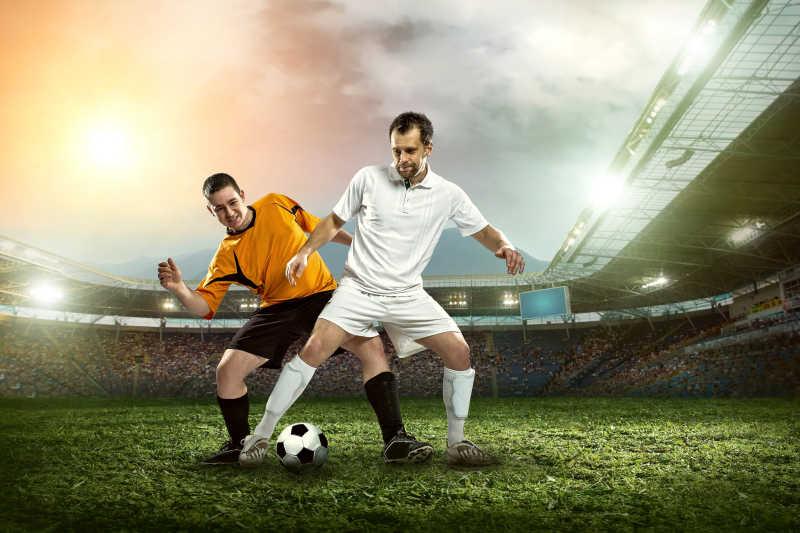 在体育场踢足球的两个足球运动员