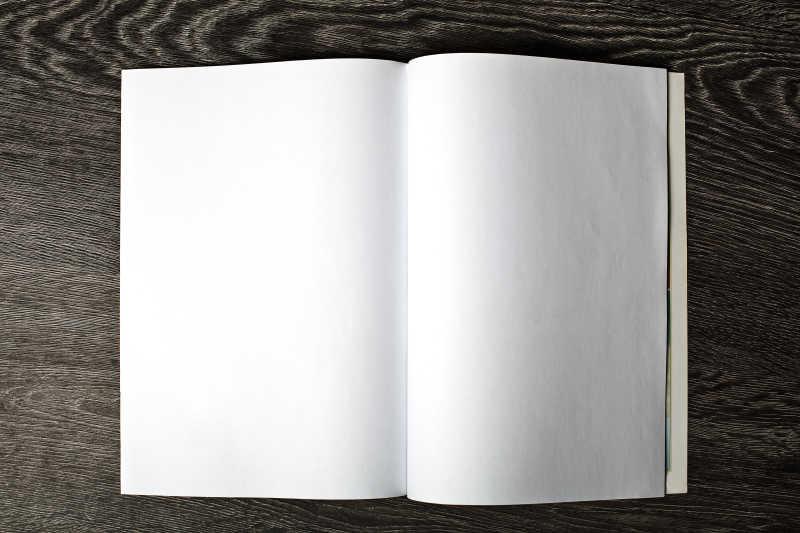 木质桌面上打开的空白日记本