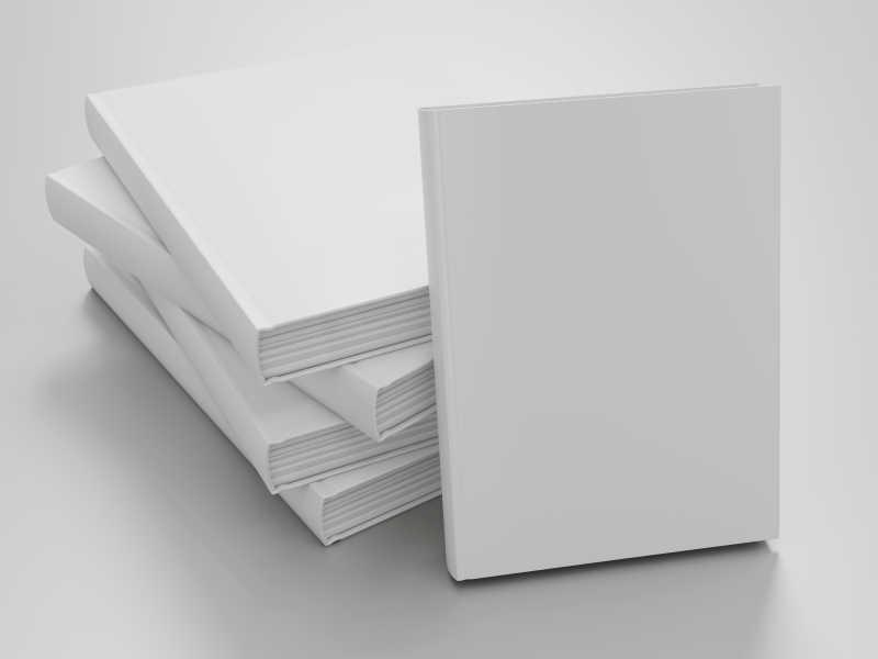 放在白色桌面上的几本白色封皮的书本