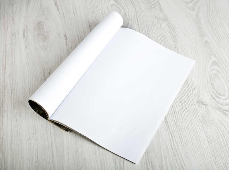 白色木制桌面上打开空白页的杂志