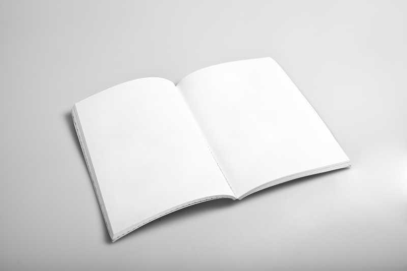 灰白色桌面上打开的空白日记本