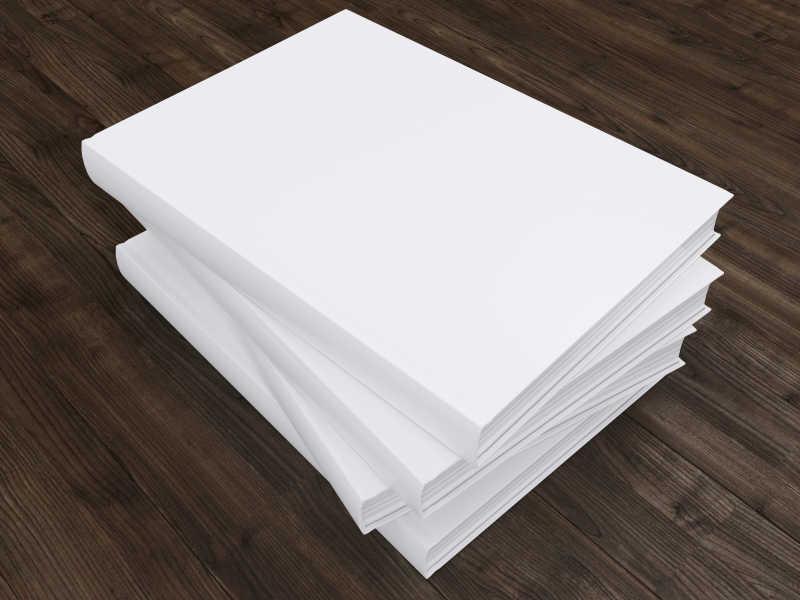 木制桌面上堆放在一起的白色书