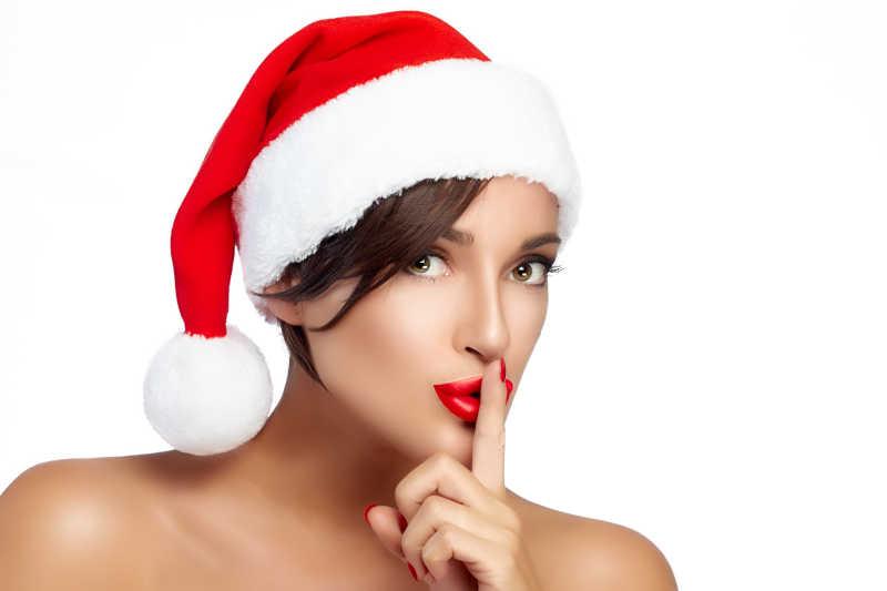 可爱的圣诞女孩在Santa的帽子做一个安静的标志