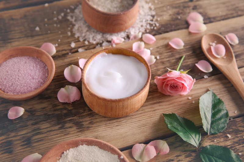 木桌上的玫瑰花瓣与木碗里的自制护肤品