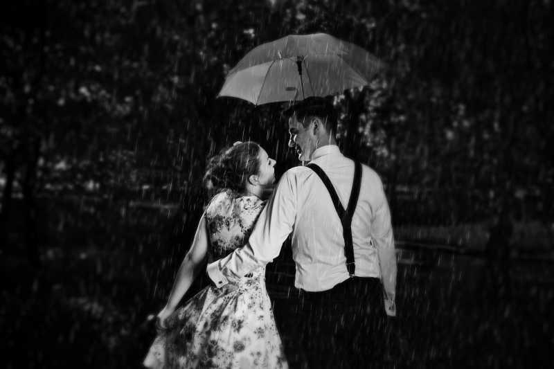 恋爱中的年轻情侣在雨中调情