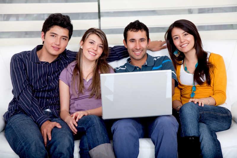 坐在沙发上的四个休闲大学生