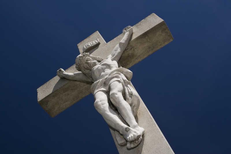深蓝色背景下耶稣被钉十字架的石像