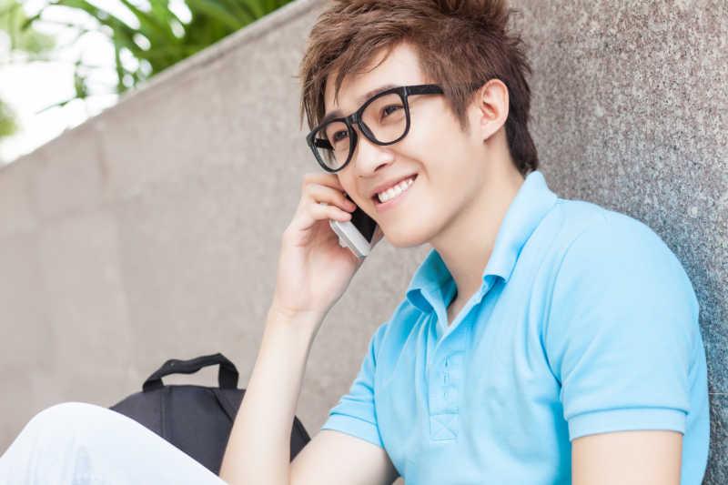 戴眼镜的年轻人再打电话