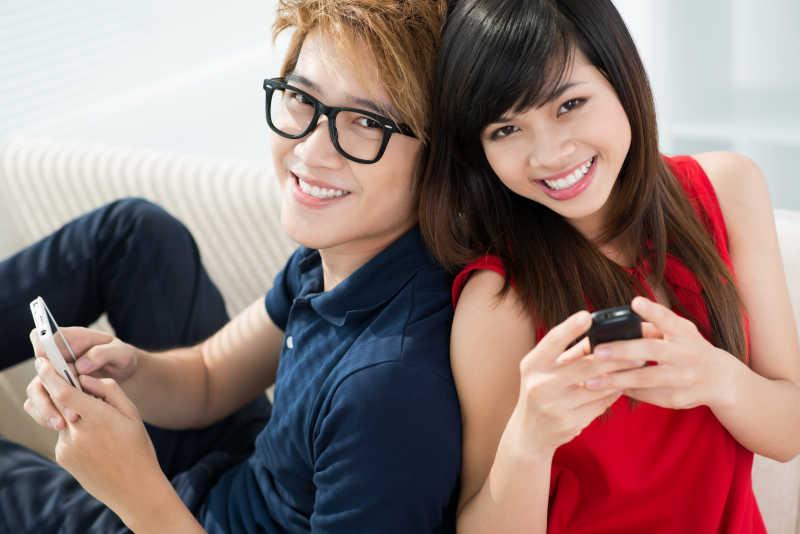 两个年轻男女拿着手机微笑着