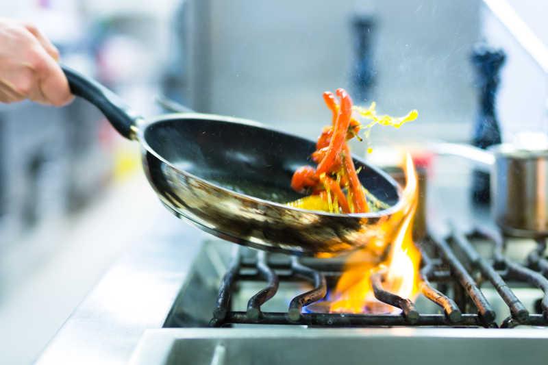 厨师在厨房用平底锅炒菜