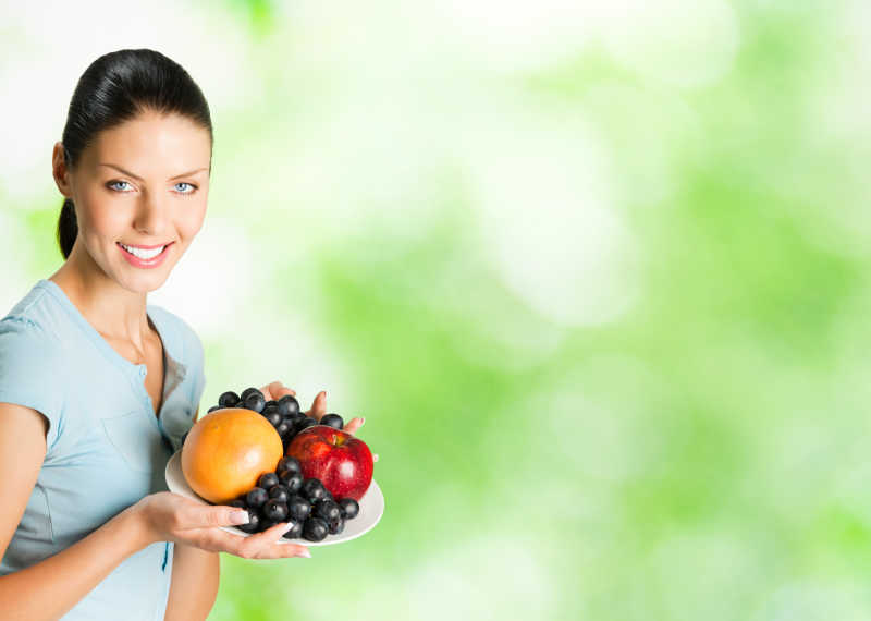 美女端着一盘水果