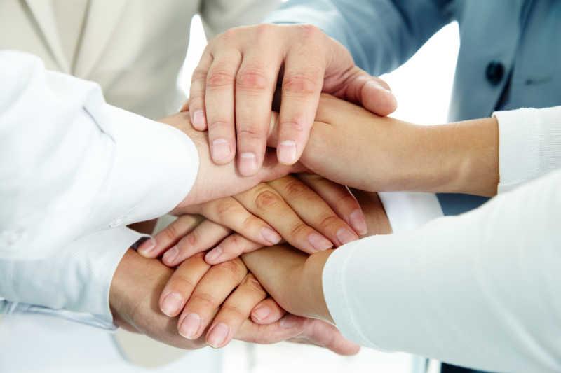 商业团队把手相叠在一起表示合作愉快