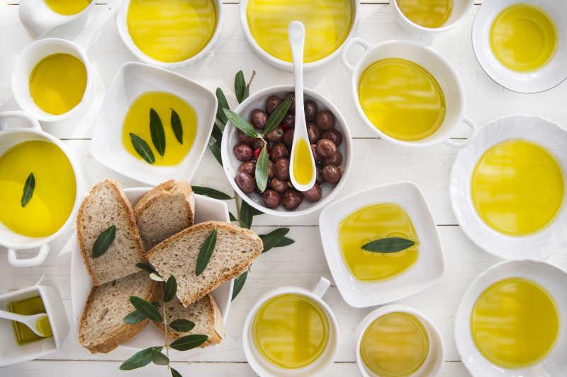 白色背景下一瓶满满的橄榄油和带着枝叶的橄榄图片素材 橄榄油和带着枝叶的橄榄创意图片素材 Jpg图片格式 Mac天空素材下载