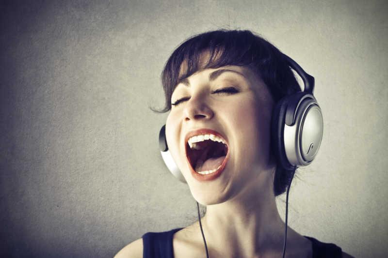 灰色背景下戴着耳机音乐演唱的女人