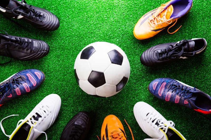 绿色的人工草坪中的很多双球鞋和足球