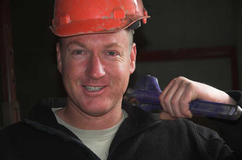 微笑的修理工带着红色安全帽肩扛蓝色扳手