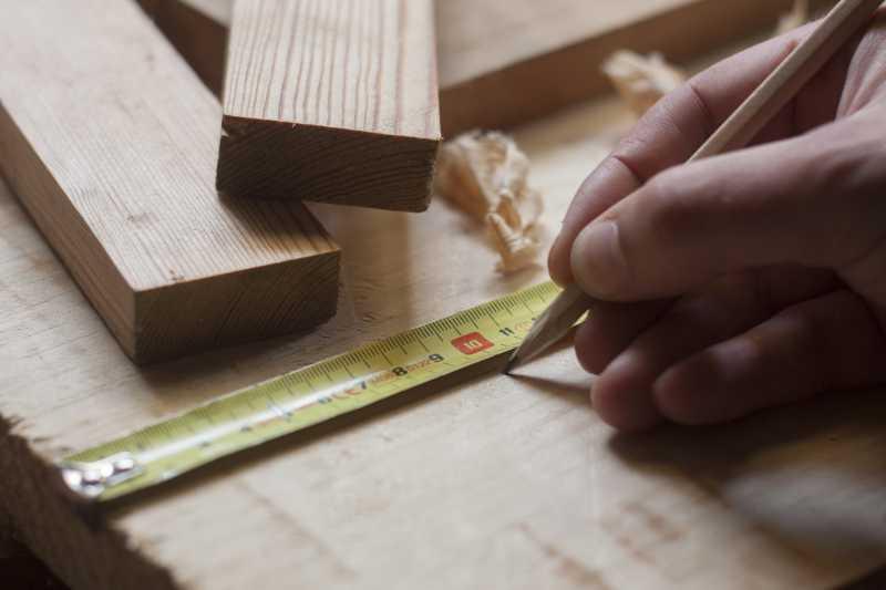 正在测量木材的木匠
