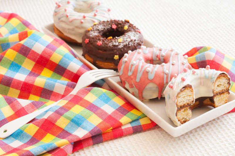 彩色桌布上白色盘子里的各种颜色的甜甜圈