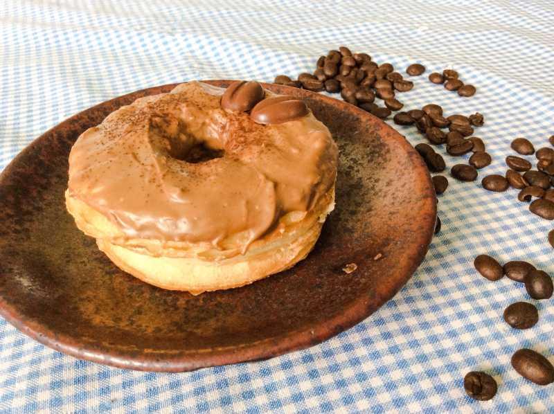蓝白色桌布上棕色盘子里的巧克力甜甜圈