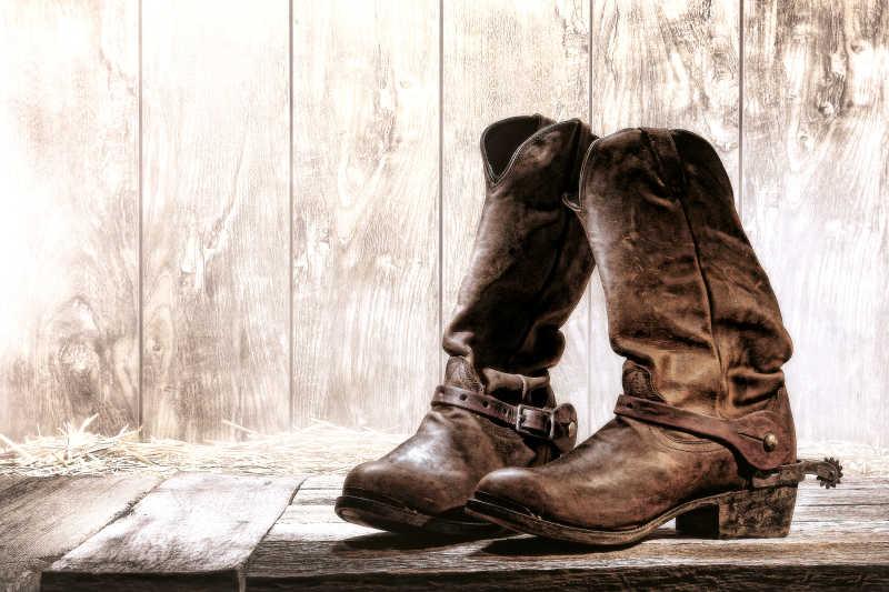 牧场上木甲板放置的一双牛仔靴