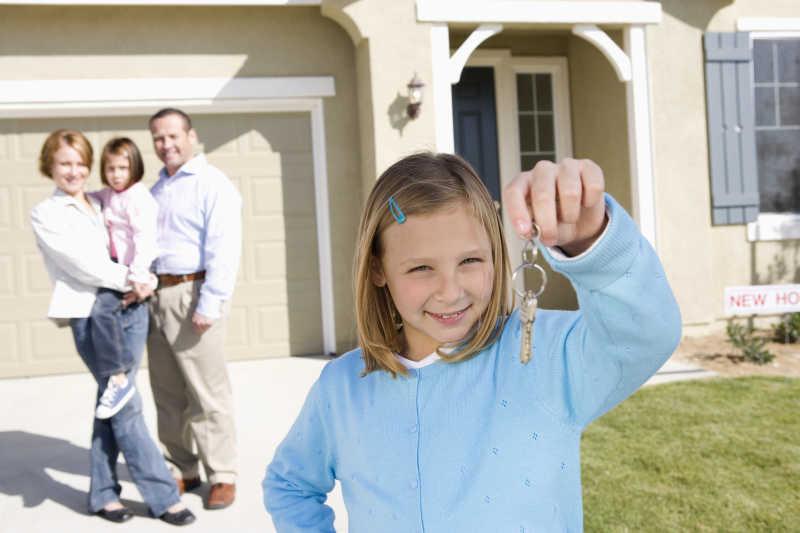 在新房子前抱着钥匙的快乐女孩