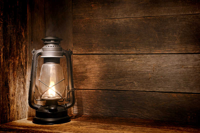 木墙和风化的木地板上老式煤油油灯