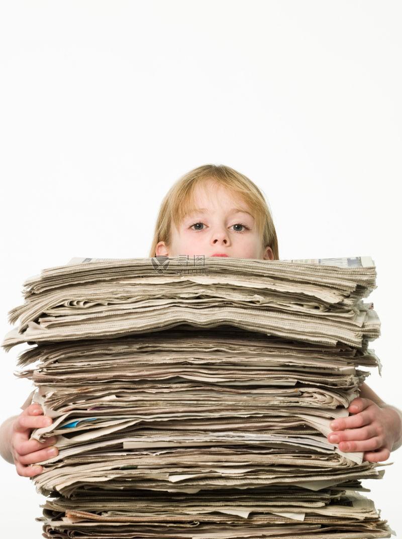 小女孩抱着高高的旧报纸