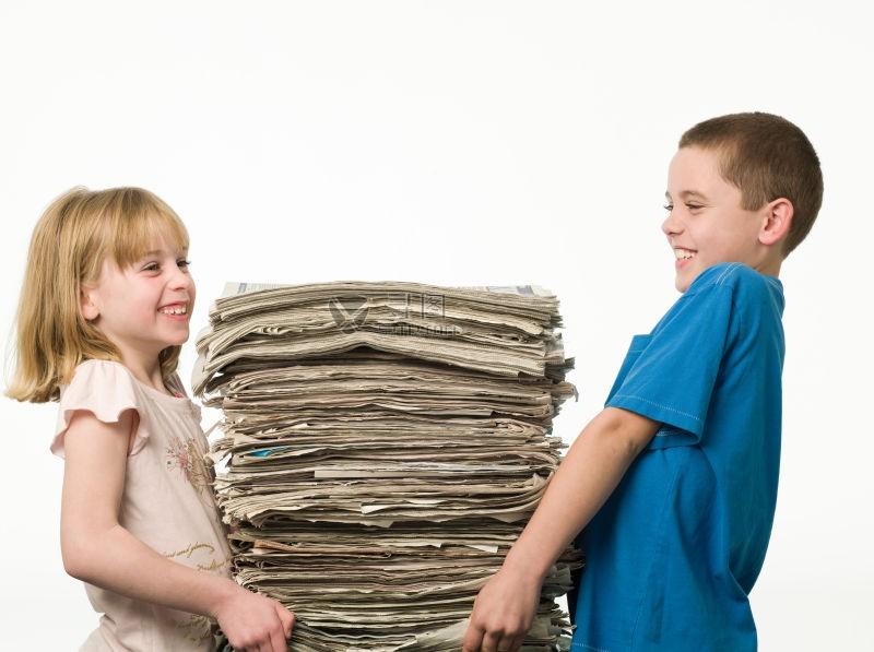 两个小孩在搬一摞厚厚的报纸