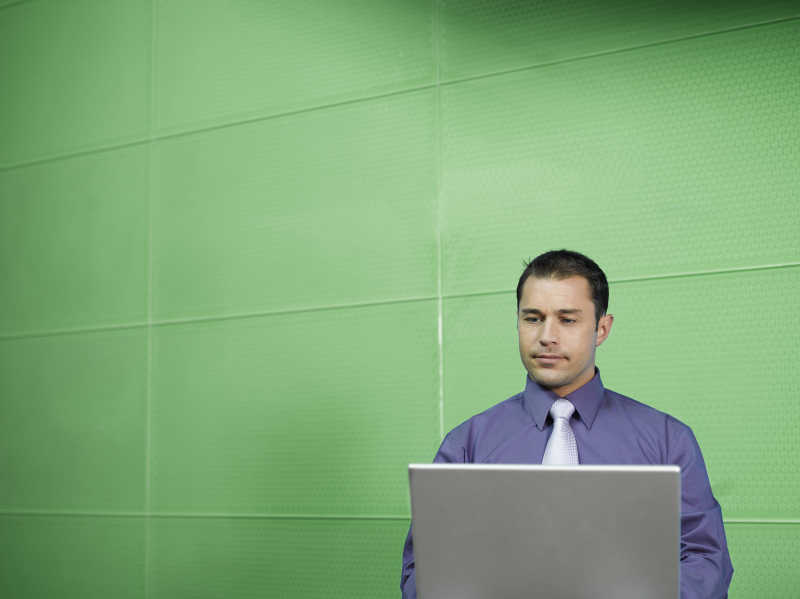 绿色墙面前的男商人