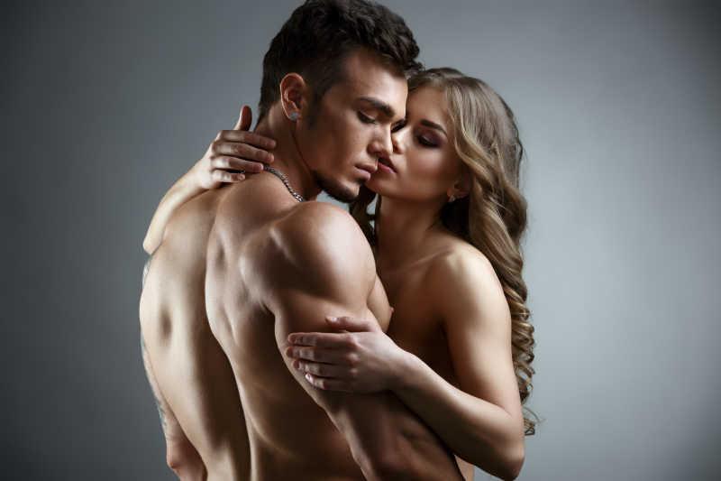 灰色背景下拥抱的半裸情侣