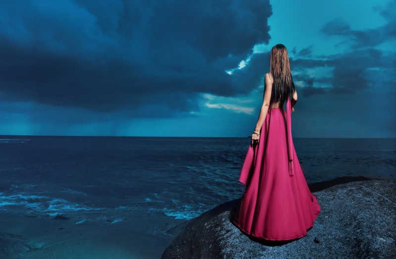 穿着礼服的的少女站在岩石上看着平静的海面