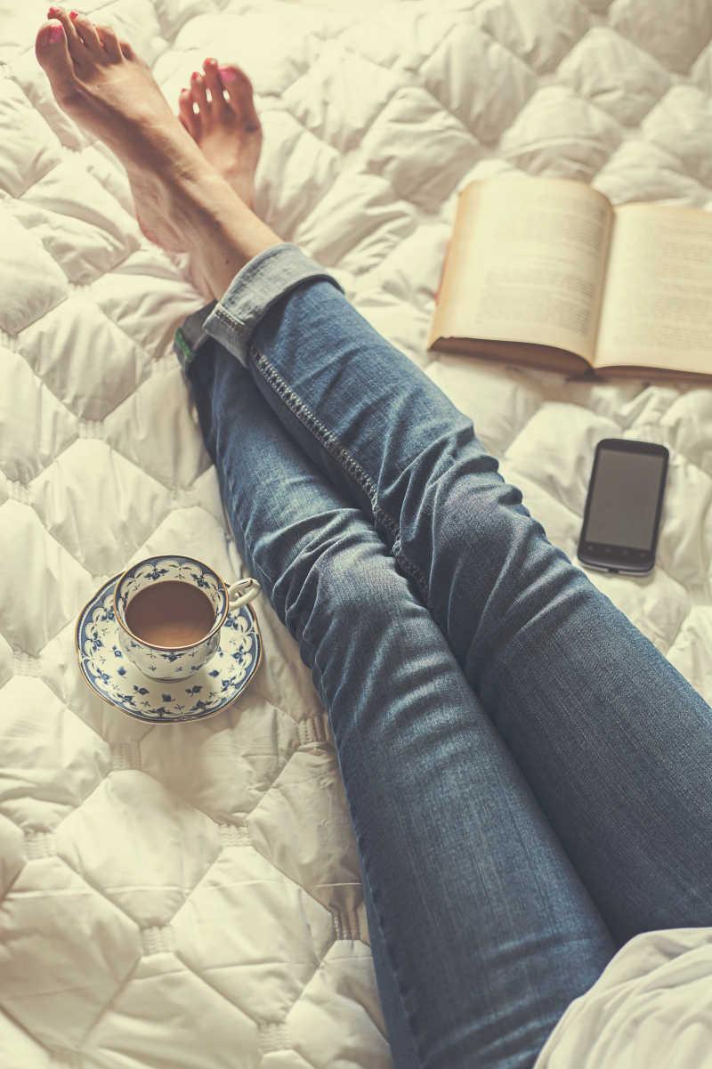 俯拍床上穿着牛仔裤的女人的腿