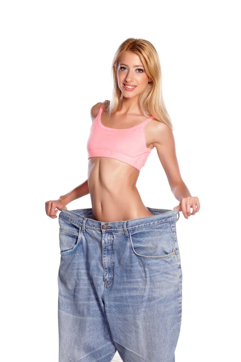 白色背景上的年轻女人穿着裤腰很大的牛仔裤