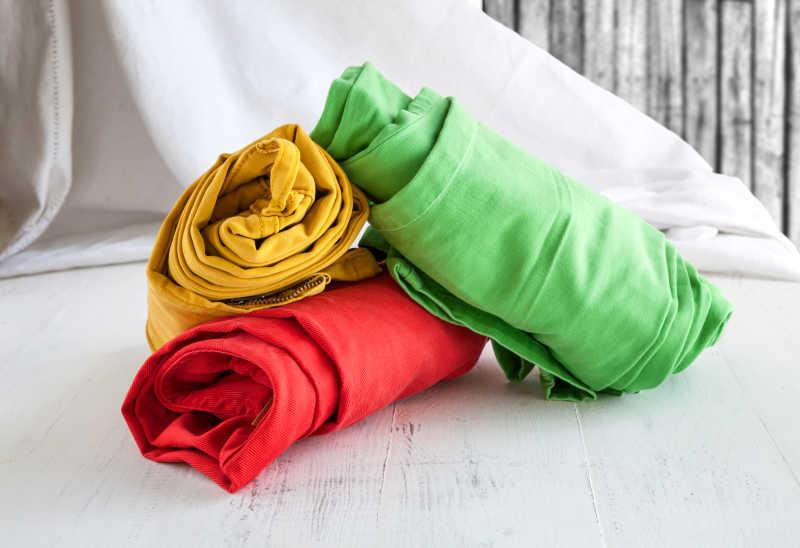 白色木桌上三条色彩鲜艳的裤子