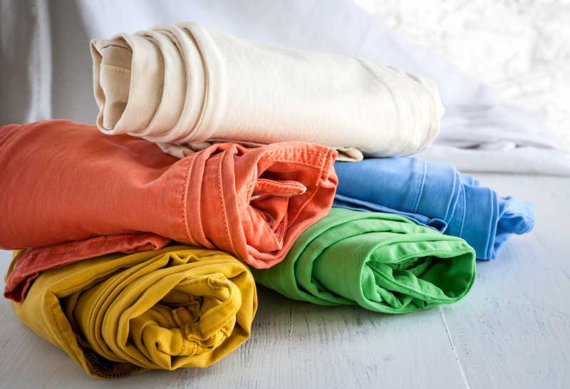 白色桌子上的卷好的五条彩色牛仔裤