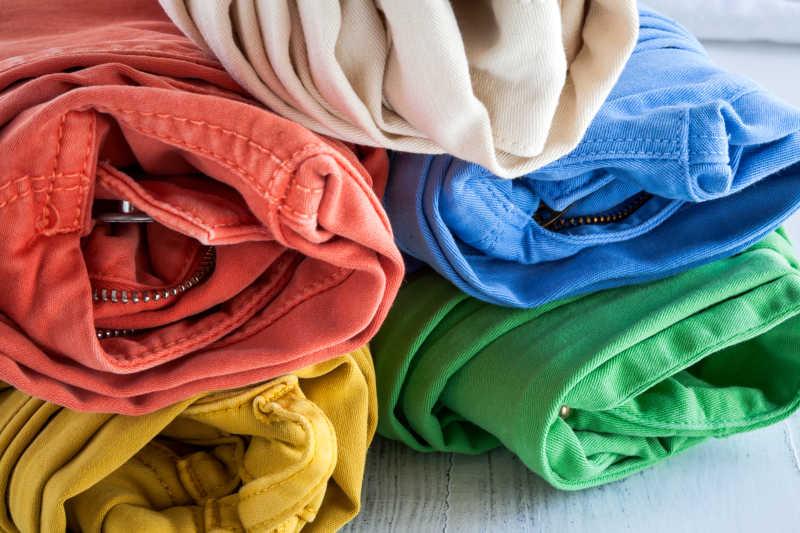 木桌上的叠好的五条彩色牛仔裤