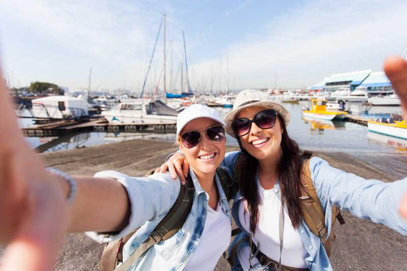 两个快乐的女性旅行者在码头自拍