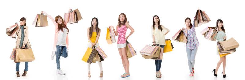 白色背景下的手拿购物袋的快乐美女们